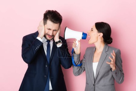 Photo for Emotional woman screaming in megaphone near bearded businessman covering ears on pink - Royalty Free Image