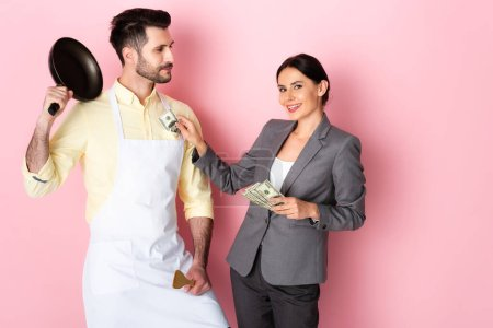 Photo for Happy businesswoman putting money in pocket of handsome man in apron holding frying pan and spatula on pink - Royalty Free Image
