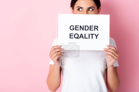 Photo for Woman in white t-shirt covering face with gender equality lettering on placard and looking away on pink - Royalty Free Image