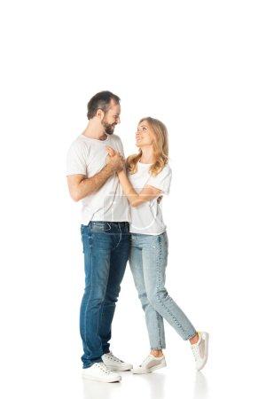 glückliches erwachsenes Paar in weißen T-Shirts, das sich umarmt und Händchen hält