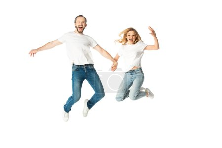 happy adult couple in white t-shirts holding hands while jumping isolated on white