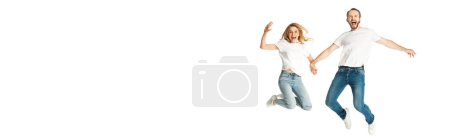 happy adult couple in white t-shirts holding hands while jumping isolated on white, panoramic shot