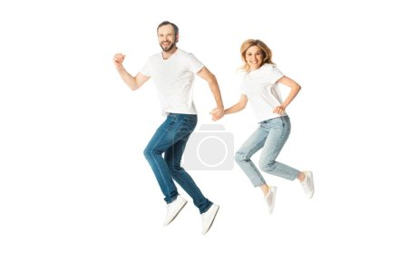 Photo for Happy adult couple in white t-shirts holding hands while jumping isolated on white - Royalty Free Image
