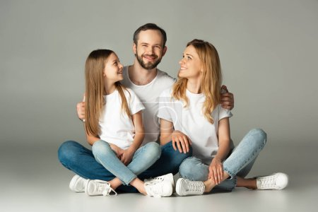 Photo for Happy family sitting on floor with crossed legs and embracing on grey background - Royalty Free Image
