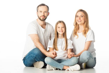 Photo for Happy family sitting on floor with crossed legs and holding hands isolated on white - Royalty Free Image