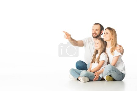 Photo for Happy family sitting on floor with crossed legs while man pointing away isolated on white - Royalty Free Image