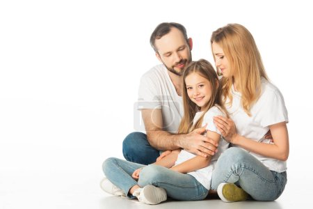 Photo for Happy family sitting on floor with crossed legs and embracing isolated on white - Royalty Free Image