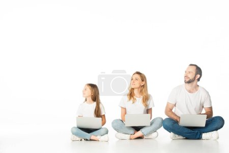 family sitting on floor with laptops on crossed legs and looking away isolated on white