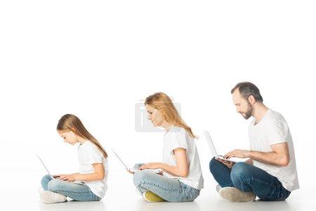 Photo pour Vue latérale de la famille assise sur le sol avec des ordinateurs portables sur les jambes croisées isolées sur blanc - image libre de droit