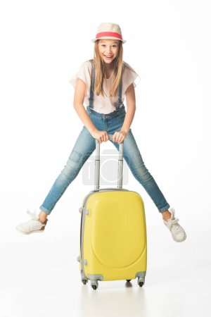 happy girl in hat jumping near yellow travel bag isolated on white