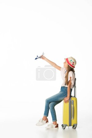 Photo for Girl in hat with plane model on yellow travel bag isolated on white - Royalty Free Image