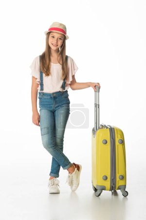 full length view of cheerful girl in hat with yellow travel bag isolated on white