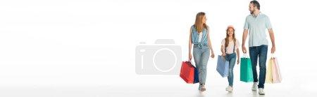 Photo pour Famille heureuse marchant avec des sacs colorés isolés sur blanc, vue panoramique - image libre de droit