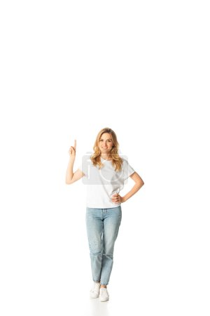 full length view of smiling attractive adult woman pointing up isolated on white