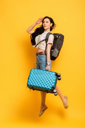 Photo for Brunette woman jumping with backpack and suitcase and looking away on yellow background - Royalty Free Image