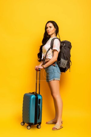 brunette woman with backpack and suitcase looking away on yellow background