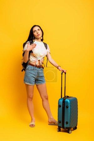 Photo pour Brunette femme avec sac à dos et valise souffrant de chaleur sur fond jaune - image libre de droit