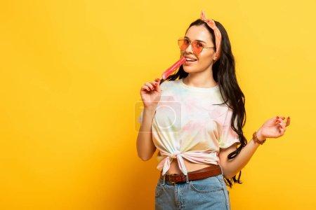 smiling stylish summer brunette girl with ice cream on yellow background