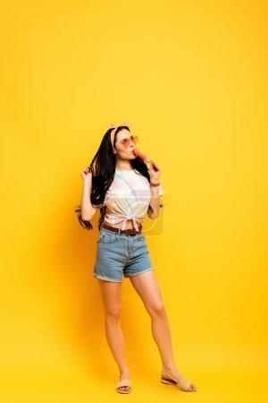 chica morena verano elegante comiendo helado sobre fondo amarillo