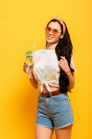 sonriente elegante chica morena de verano con refrescante cóctel sobre fondo amarillo