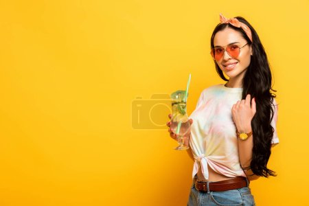 Photo for Smiling stylish summer brunette girl with refreshing cocktail on yellow background - Royalty Free Image