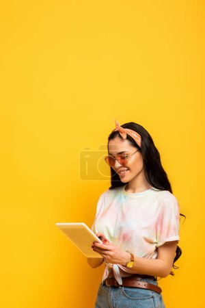 Photo for Smiling stylish summer brunette girl using digital tablet on yellow background - Royalty Free Image