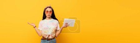 Photo pour Confus élégant été brunette fille tenant tablette numérique sur fond jaune, plan panoramique - image libre de droit