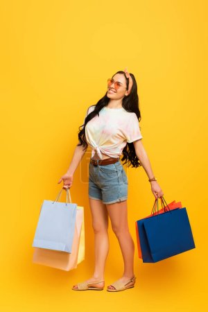 smiling stylish summer brunette girl with shopping bags on yellow background