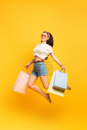 Photo for Full length view of smiling stylish summer brunette girl jumping with shopping bags on yellow background - Royalty Free Image