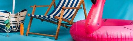Photo pour Vue rapprochée de chaise longue rayée près de flamant rose gonflable, écran solaire, sac de plage et cocktail sur fond bleu, vue panoramique - image libre de droit