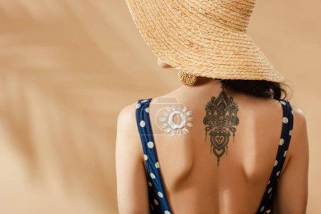 Photo pour Femme en maillot de bain à pois et chapeau de paille avec soleil dessiné et tatouage sur le dos sur fond beige - image libre de droit