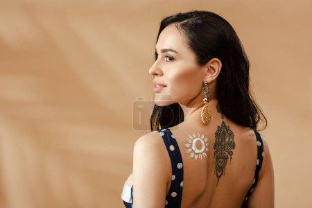 Photo pour Vue arrière de la femme brune sexy en maillot de bain à pois avec soleil dessiné en crème solaire et tatouage sur le dos sur fond beige - image libre de droit