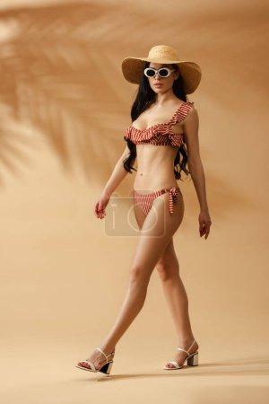 Photo pour Femme brune sexy à la mode en maillot de bain rayé, chapeau de paille et lunettes de soleil marchant sur fond beige - image libre de droit