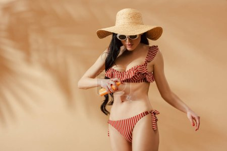 Photo for Sexy brunette woman in striped swimsuit applying sunscreen on belly on beige background - Royalty Free Image