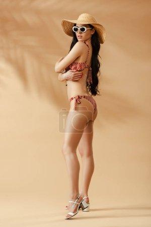 Photo pour Vue latérale de la femme brune sexy à la mode en maillot de bain rayé, chapeau de paille et lunettes de soleil sur fond beige - image libre de droit