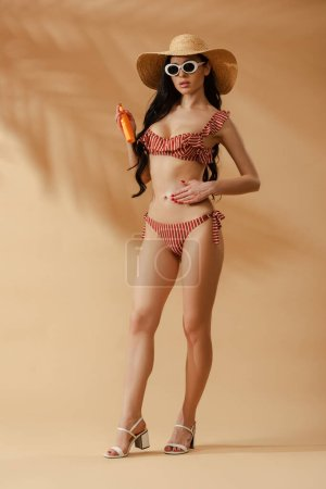 Photo pour Sexy femme brune en maillot de bain rayé appliquant de la crème solaire sur le ventre sur fond beige - image libre de droit