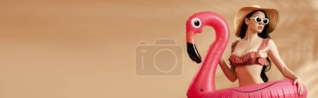 sexy brunette woman in striped swimsuit, sunglasses and straw hat with inflatable flamingo on beige background, panoramic shot