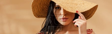 Photo for Sexy brunette woman in striped swimsuit and straw hat on beige background, panoramic shot - Royalty Free Image