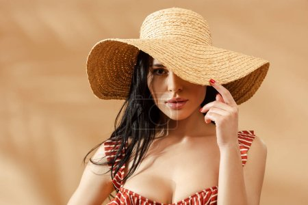 sexy brunette woman in striped swimsuit and straw hat on beige background