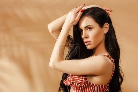 Photo pour Sexy femme brune en maillot de bain rayé posant sur fond beige - image libre de droit