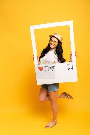 smiling brunette girl in summer outfit posing in social network frame on yellow background