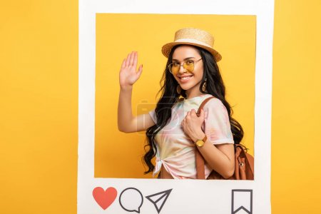 happy brunette girl in summer outfit waving hand in social network frame on yellow background