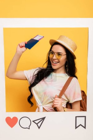 happy brunette girl in summer outfit holding air ticket in social network frame on yellow background