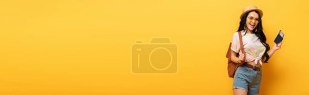Photo for Happy brunette girl in summer outfit holding air ticket on yellow background, panoramic shot - Royalty Free Image