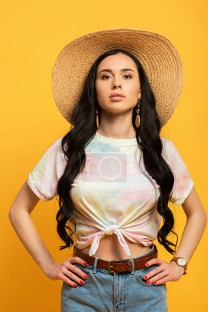 brunette girl posing in straw hat with hands on hips on yellow background