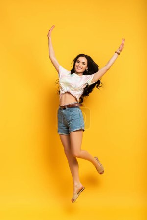 Photo for Full length view of happy brunette girl jumping on yellow background - Royalty Free Image