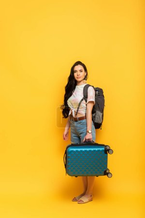brunette girl with suitcase and backpack on yellow background