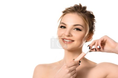 Photo for Smiling naked beautiful blonde woman with makeup and black nails holding beige lip gloss isolated on white - Royalty Free Image