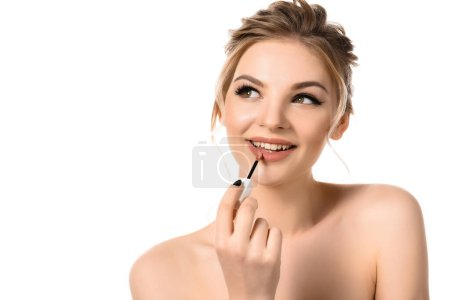 Photo for Smiling naked beautiful blonde woman with makeup and black nails applying beige lip gloss isolated on white - Royalty Free Image