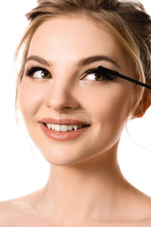 Photo for Smiling beautiful blonde woman applying mascara isolated on white - Royalty Free Image